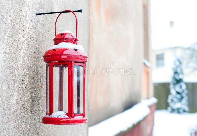 Lanterna rossa d'annata della candela di inverno di Natale che appende sulla vite fotografia stock libera da diritti