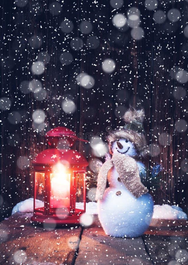 lanterna rossa d'annata di natale e pupazzo di neve in precipitazioni nevose - christma immagine stock libera da diritti