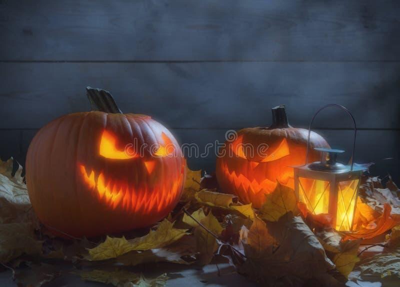 Lanterna spettrale della presa o delle zucche fra le foglie secche sul recinto di legno fotografia stock