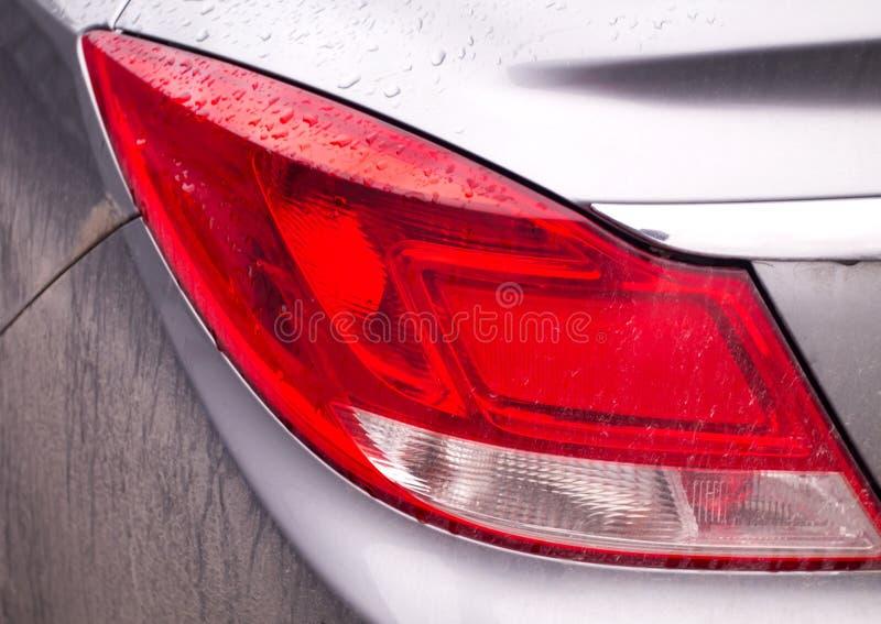 Lanterna traseira do carro nos pingos de chuva e na sujeira imagens de stock royalty free
