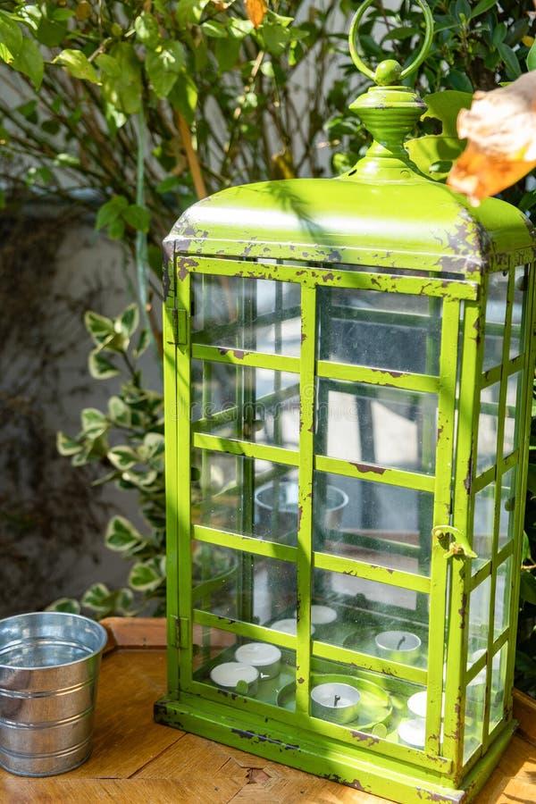 Lanterna verde con le candele dentro sulla tavola di legno Candeliere con decorativo d'annata fotografie stock