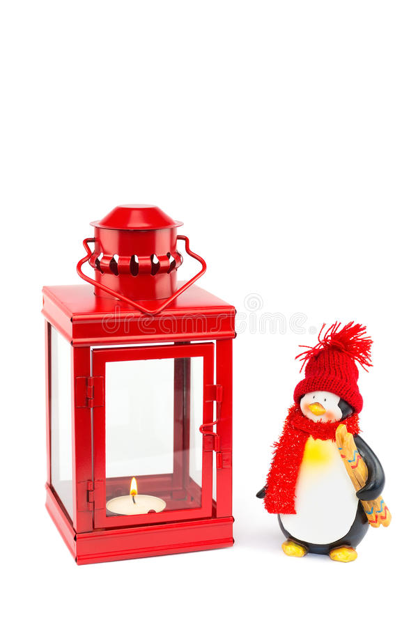 Lanterna vermelha com a estatueta do pinguim no branco fotografia de stock