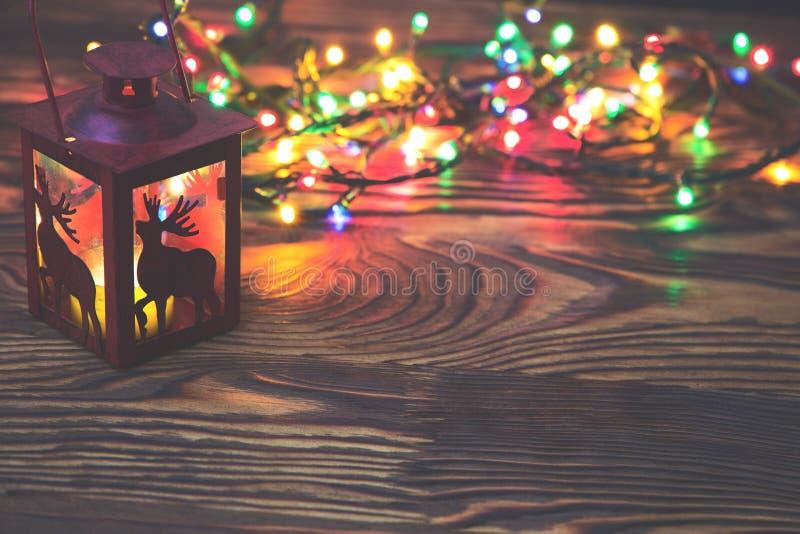 A lanterna vermelha decorativa do metal com um entalhe dos cervos iluminou-se por uma vela de incandescência com luz de Natal e p imagens de stock