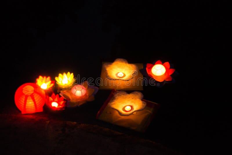 Lanternas da vela que flutuam em um rio entre reflex?es coloridas durante a noite foto de stock royalty free