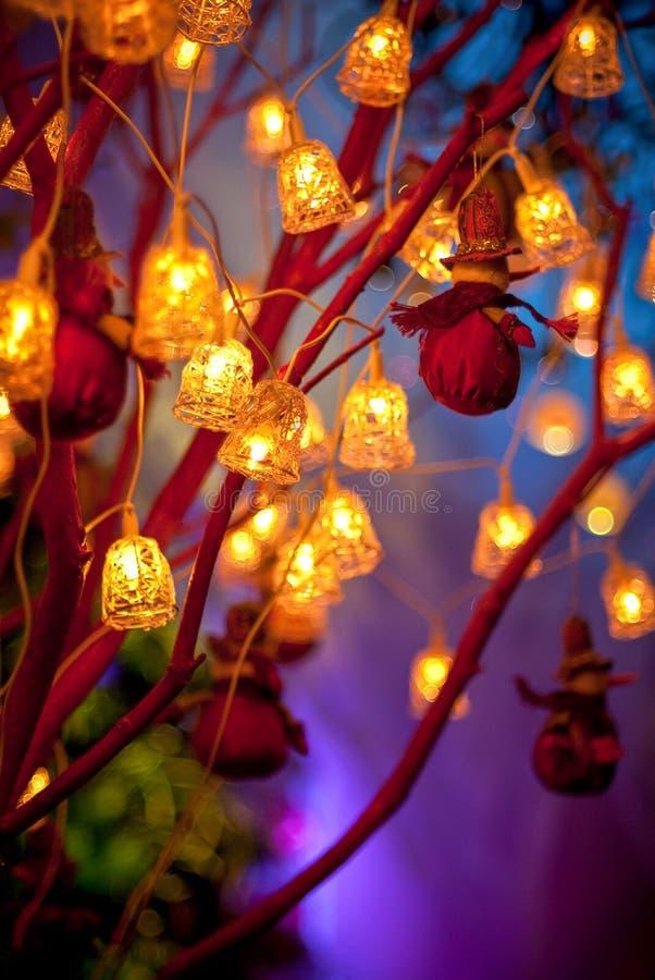 Lanternas e sinos amarelos do Natal nos ramos fotografia de stock royalty free
