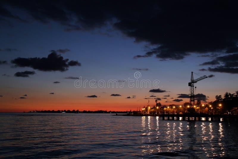 Lanternas no cais da estação naval contra o céu durante o por do sol imagens de stock