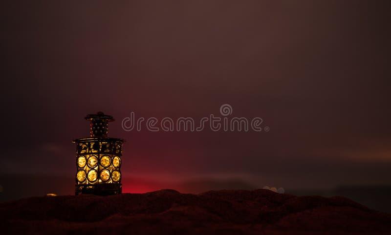 Lanterne arabe ornementale avec la bougie br?lante rougeoyant la nuit Carte de voeux de f?te, invitation pour le mois saint musul photo libre de droits