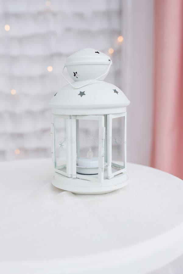 Lanterne blanche avec une bougie à l'intérieur sur une nappe blanche Chandelier avec les étoiles décoratives photos libres de droits