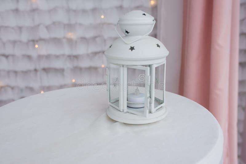 Lanterne blanche avec une bougie à l'intérieur sur une nappe blanche Chandelier avec les étoiles décoratives images libres de droits