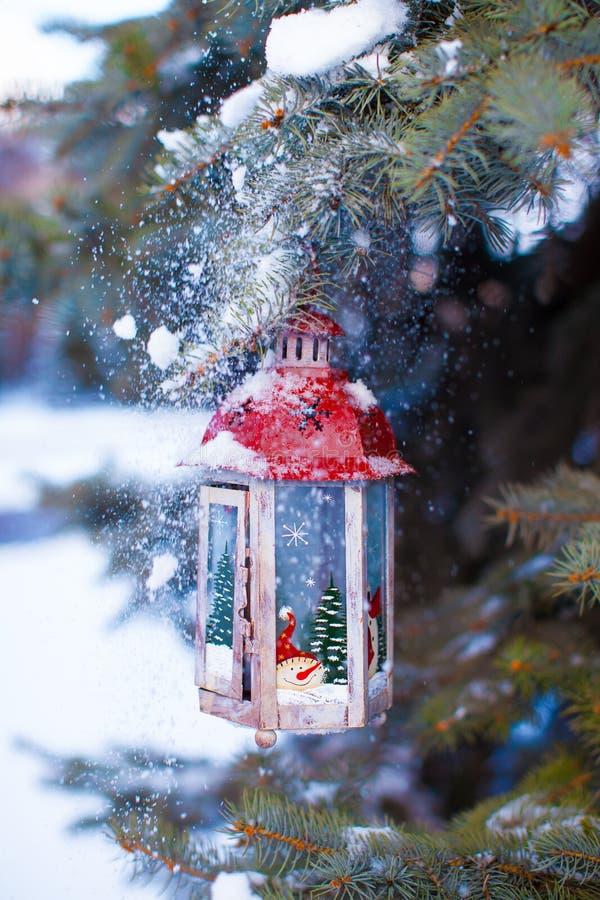 Lanterne décorative de Noël sur la branche de sapin dans la neige photo stock