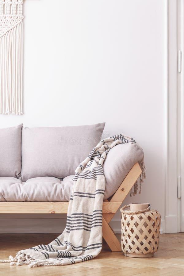 Lanterne de contreplaqué à côté d'un sofa en bois avec les coussins gris et d'une couverture dans un intérieur simple de salon photo libre de droits