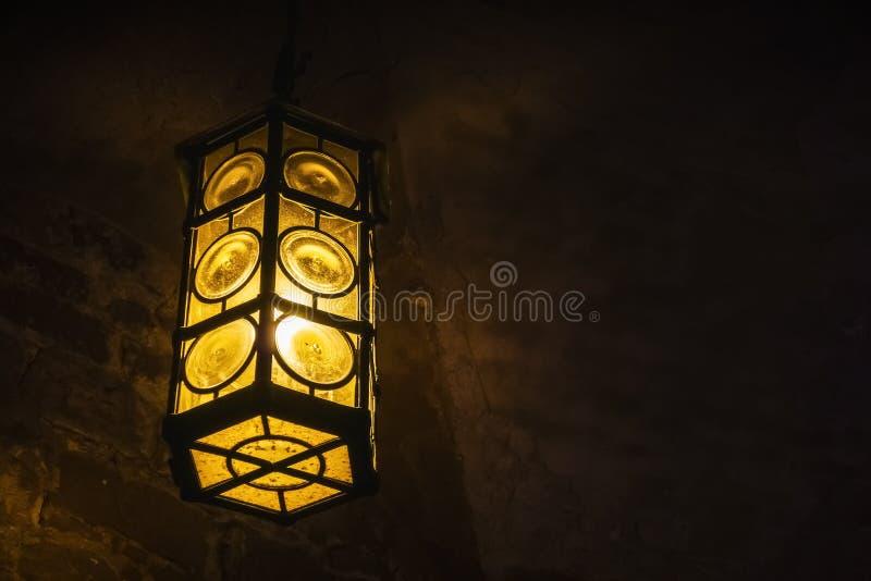 Lanterne de fer travaillé accrochant dans une chambre forte médiévale de château photo libre de droits