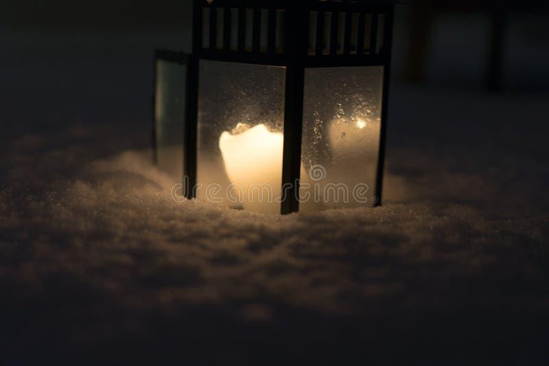 Lanterne de Noël avec la bougie brûlante sur la scène de soirée de neige images stock