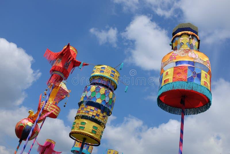 Lanterne di carta brillantemente colorate contro un cielo blu nuvoloso immagine stock