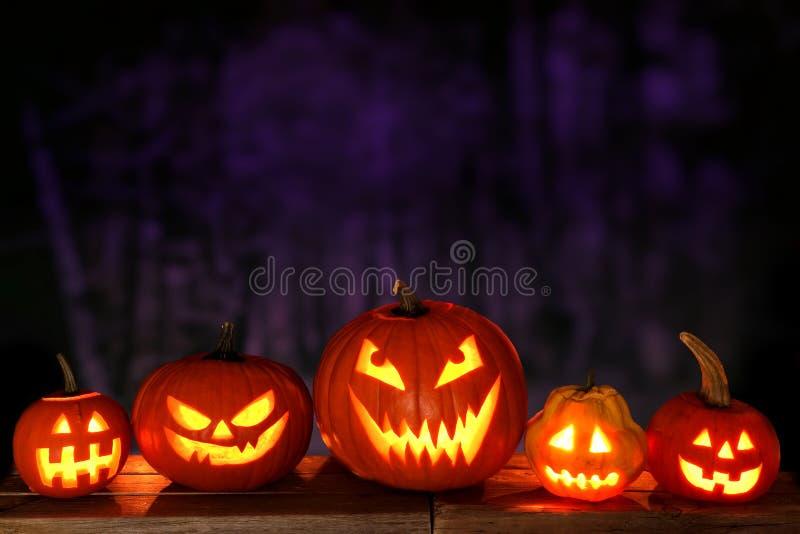 Lanterne di Halloween Jack o alla notte contro un fondo spettrale immagine stock libera da diritti