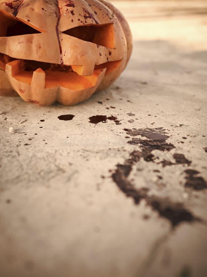 Lanterne du cric o de Halloween avec les taches de sang rouges sur la terre photos libres de droits