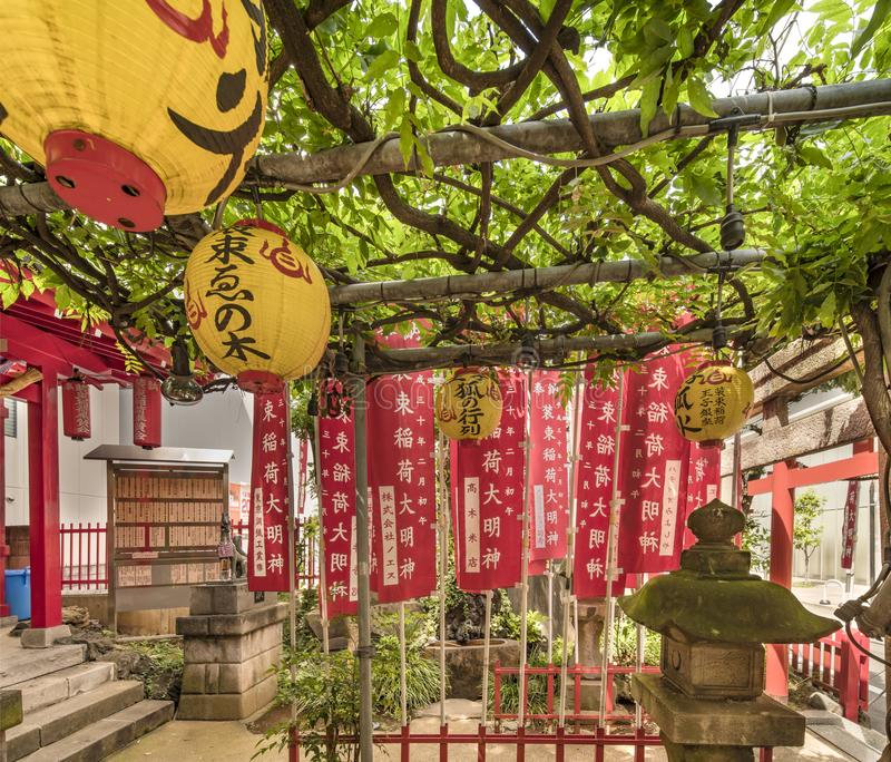 Lanterne en pierre couverte de la mousse verte dans un petit tombeau de Shinto Shozoku Inari photos stock