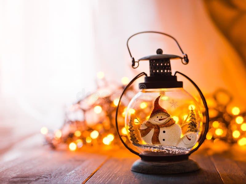Lanterne en verre avec les cadeaux de Noël brûlants de bougies et une guirlande rougeoyante sur une table en bois photo libre de droits
