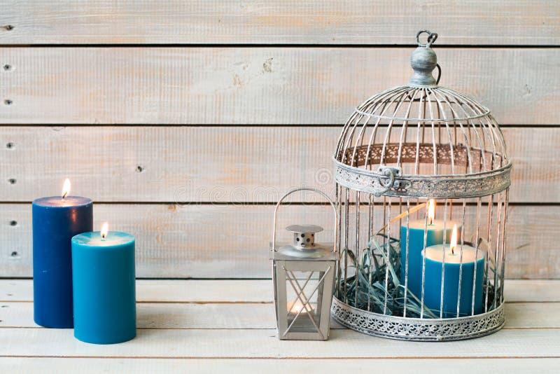 Lanterne et bougies bleues au-dessus du fond en bois blanc Copiez Spac image libre de droits