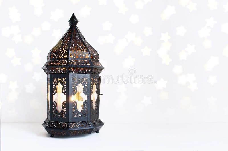 Lanterne marocaine et arabe foncée ornementale sur la table blanche La bougie brûlante, bokeh éclatant allume des étoiles salutat image libre de droits