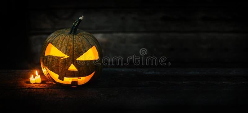 Lanterne principale de cric de potiron de Halloween avec les bougies brûlantes sur le fond déprimé foncé images libres de droits