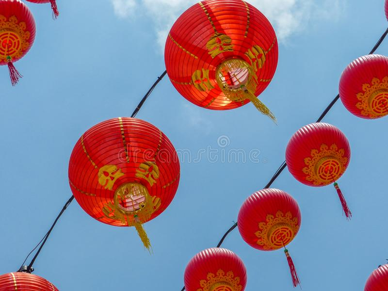 Lanterne rosse cinesi che appendono contro un chiaro cielo blu immagini stock libere da diritti