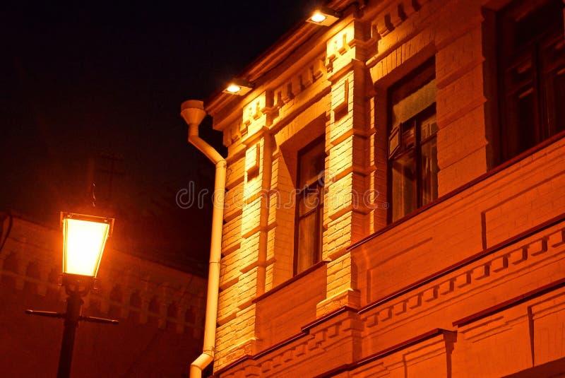 Lanterne rouge rougeoyante sur un poteau sur une rue de nuit près du mur d'une maison photographie stock