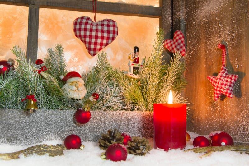 Lanterne rustique avec des lueurs d'une bougie pour Noël - classique en rouge image stock