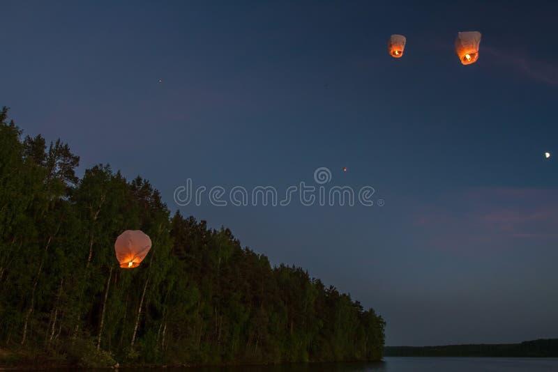 Lanternes chinoises de vol, vol au-dessus du lac dans l'obscurité images stock