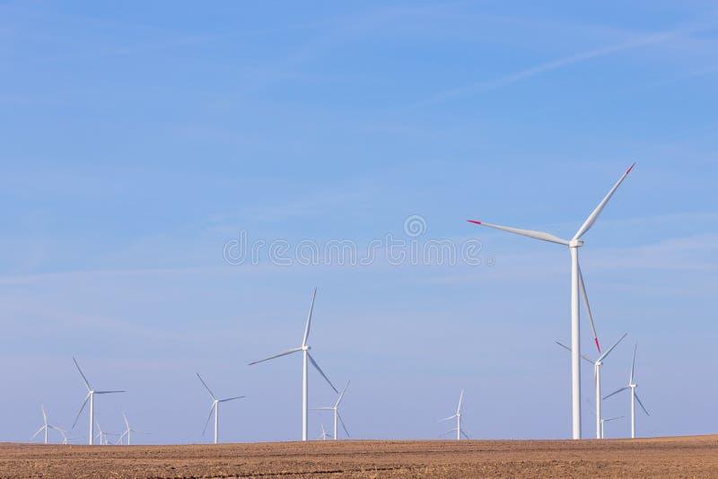 Lantgård av väderkvarnturbiner på jordbruks- fält med blå himmel i bakgrund förnybar turbinwind för energi arkivfoton