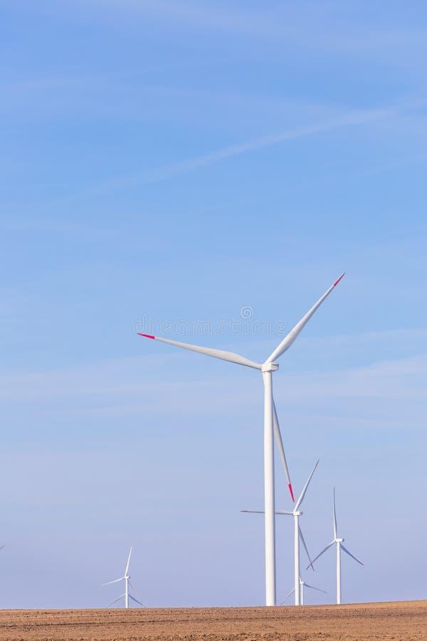 Lantgård av väderkvarnturbiner på jordbruks- fält med blå himmel i bakgrund förnybar turbinwind för energi royaltyfria bilder