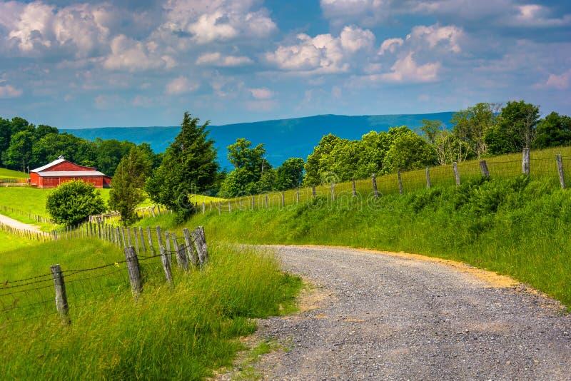 Lantgårdfält längs en grusväg i den lantliga Potomac Skotska högländerna av arkivbild