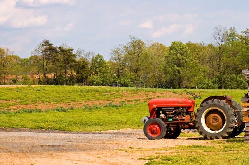 lantgårdfält nära den röda traktoren royaltyfria foton