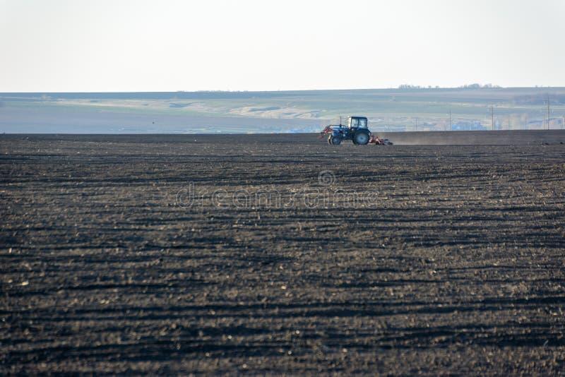Lantgårdtraktor med plogen i ett fält på en lantgård i den soliga dagen Bonde i traktoren som f?rbereder land Det är säsongen av  royaltyfri foto