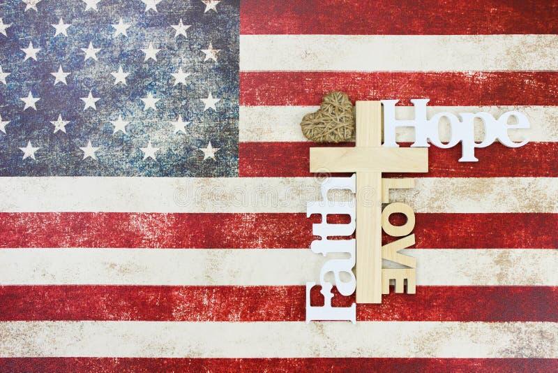 Lantlig amerikanska flaggan med träkorset fotografering för bildbyråer