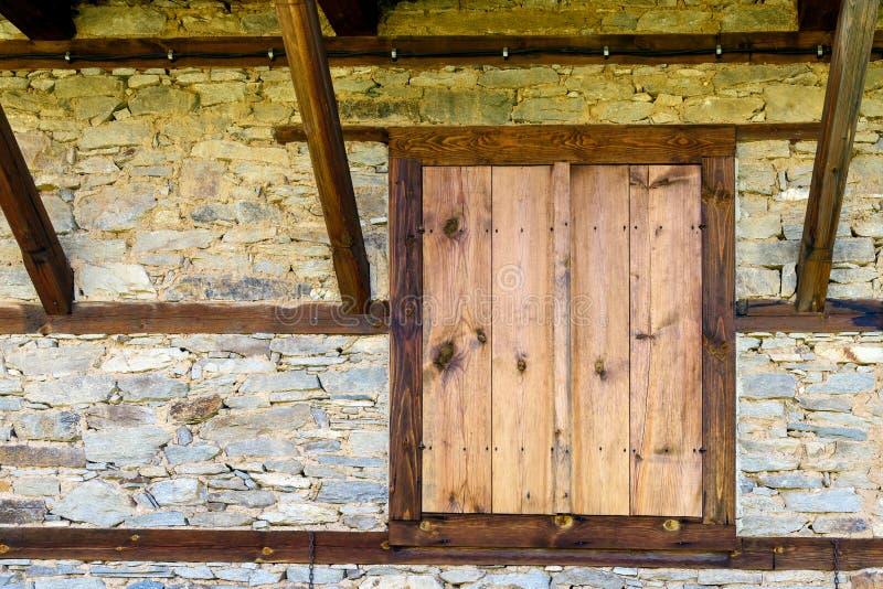 Lantlig bakgrund med stängda träslutare på stenväggen arkivfoton