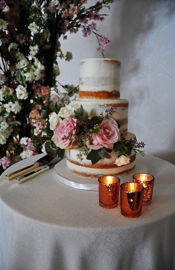 Lantlig bröllopstårta och guld- stearinljus arkivfoton