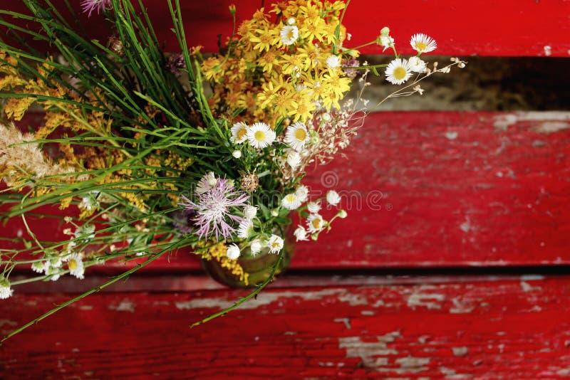 Lantlig bukett av lösa blommor på gammal träröd bänk på countr arkivbild
