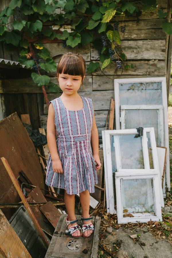 Lantlig flicka bland det gamla träavfallet royaltyfri bild