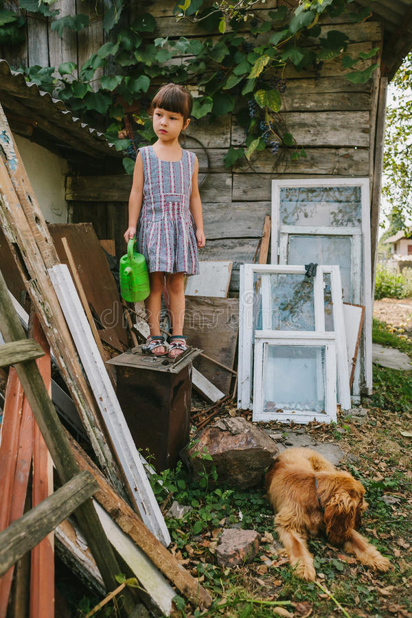 Lantlig flicka med hennes hund bland det gamla träavfallet royaltyfri bild