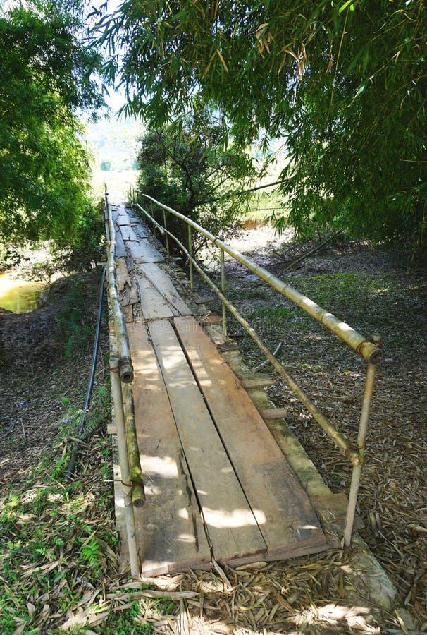 Lantlig fotbro med bamburäcket och träplankor i lantliga Laos fotografering för bildbyråer