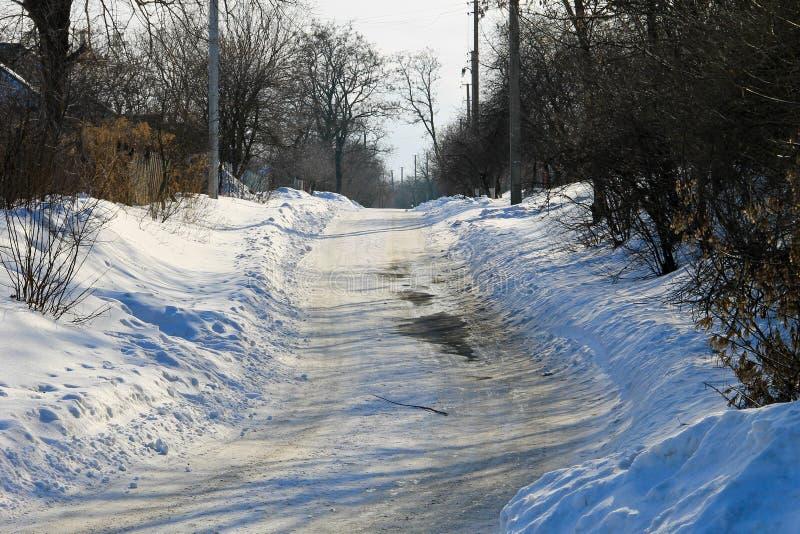 Lantlig fryst hal asfaltväg arkivfoto