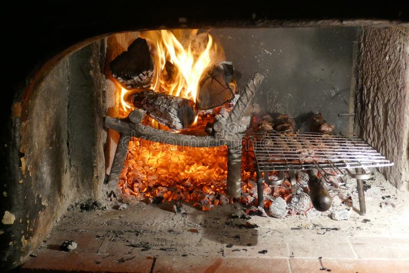Lantlig grillfestugn med gallret Ljus flammor, trä, glöd och aska arkivbilder