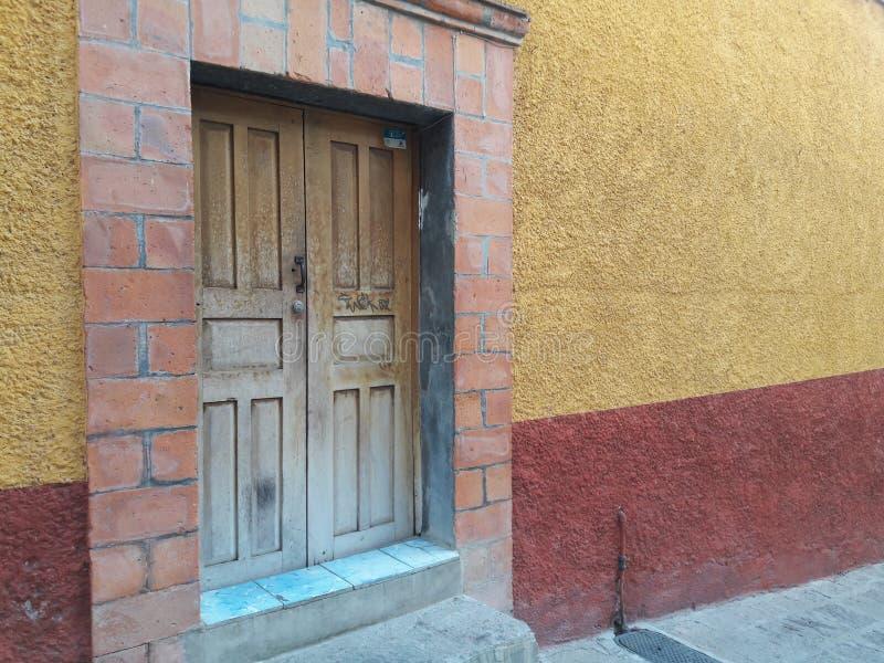Lantlig Hand-sniden antik trädörr i urinnevånare texturerad mexicansk tegelsten- och stuckaturvägg med guld, rost, blåa bakgrunds arkivfoto