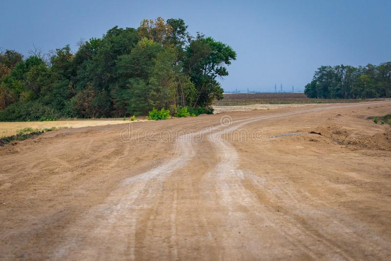 Lantlig inte asfalterad väg som passerar till och med ett jordbruks- fält royaltyfri fotografi