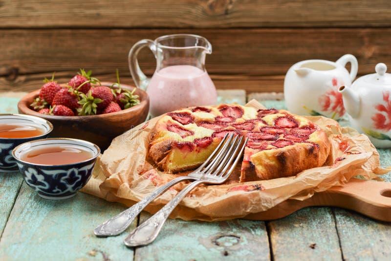 Lantlig jordgubbepaj i bakningpapper med nytt bär och te royaltyfria bilder