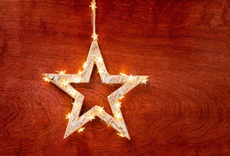 Lantlig jul smyckar stjärnan som slås in i ljus på rött arkivbilder