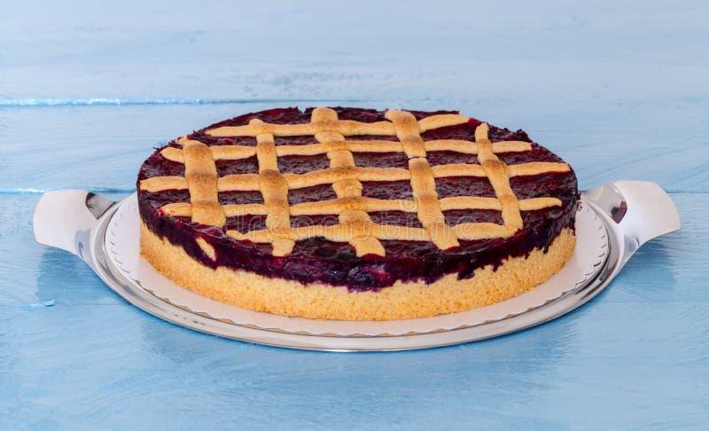 Lantlig kaka för raster med skogbär på blått trä royaltyfri foto