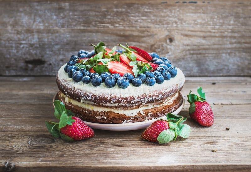 Lantlig kryddig ljust rödbrun kaka med gräddostfyllning, nya jordgubbar och blåbär över en grov wood bakgrund royaltyfria bilder