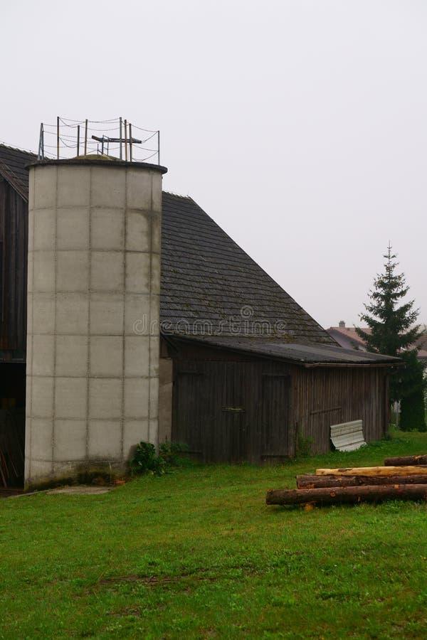 Lantlig ladugård i en molniga typiska Österrike, mulen regnig dag royaltyfri fotografi